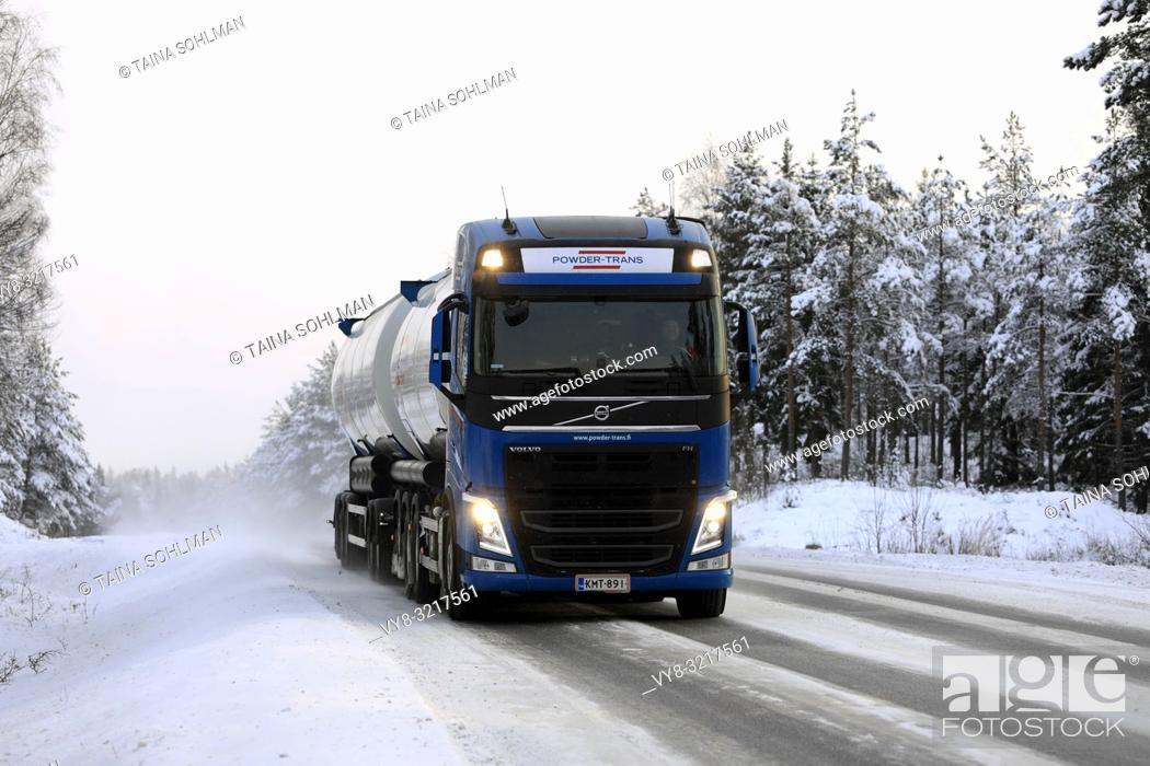 Stock Photo: Salo, Finland - December 23, 2018: Volvo FH bulk transport truck up front driving on snowy road in arctic conditions, with high beam lights on briefly.