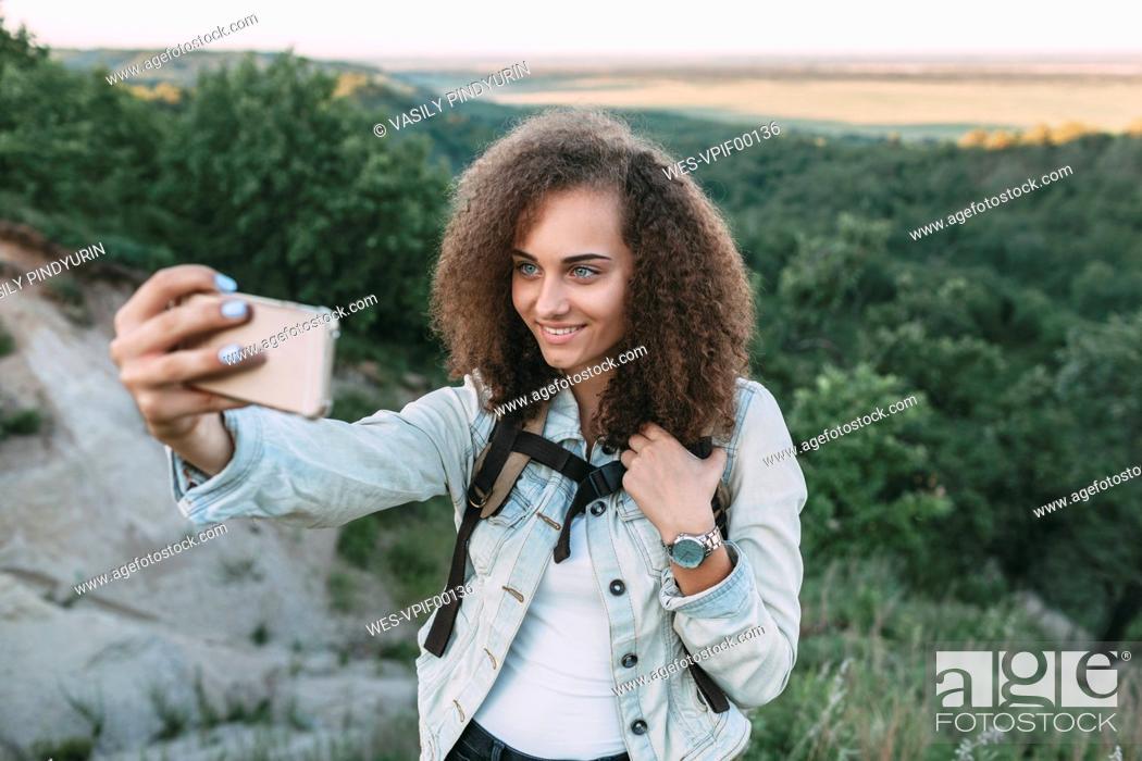 Stock Photo: Smiling teenage girl taking selfie in nature.