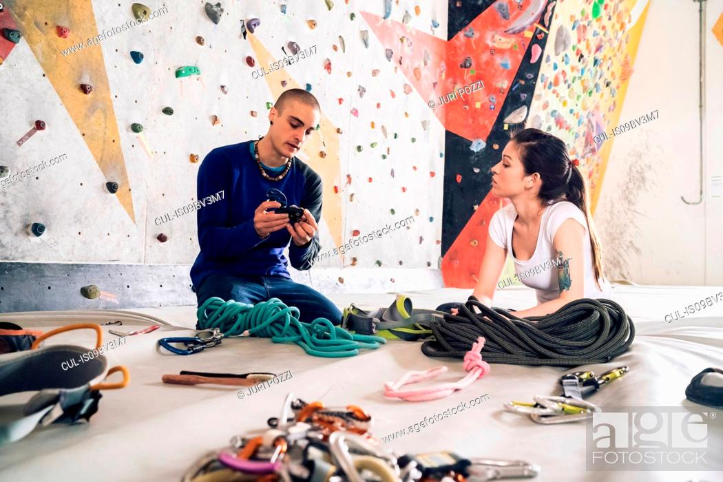 Stock Photo: Climber friends on crash pad working with and learning about climbing equipment.