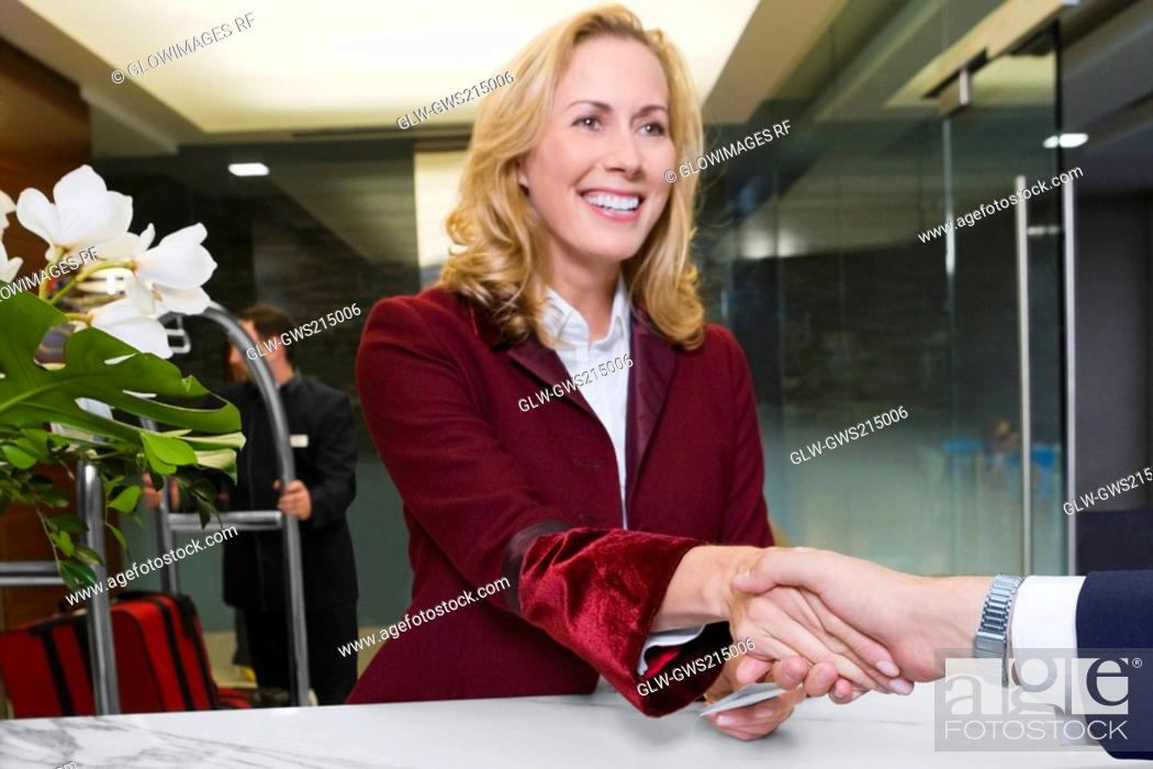 Stock Photo: Receptionist giving the cardkey to a customer.