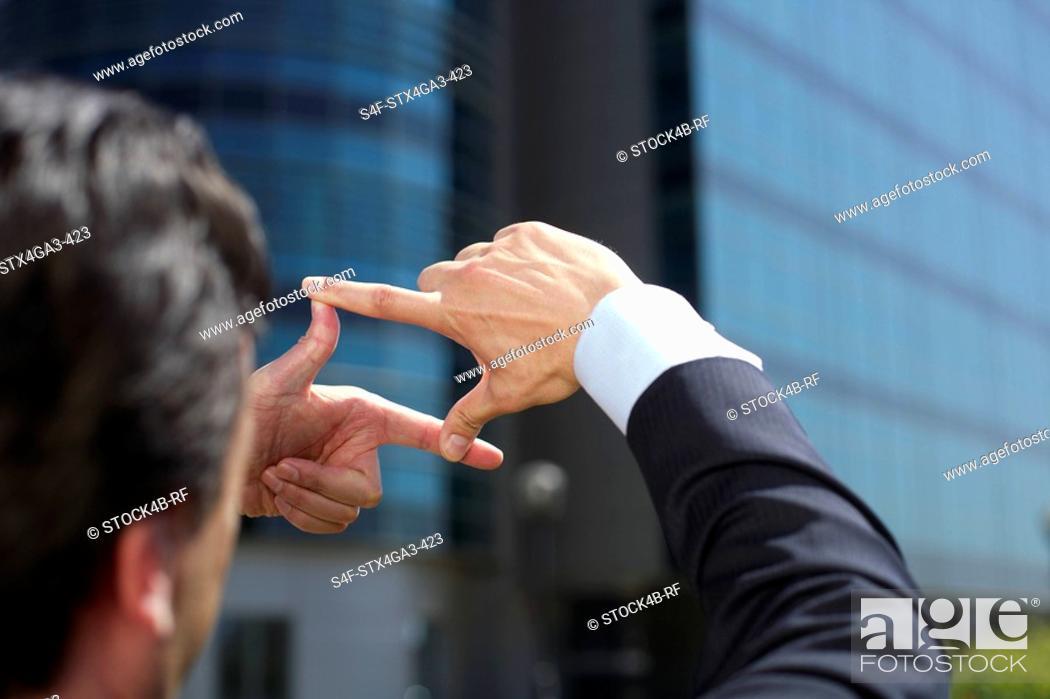 Stock Photo: Man watching through his fingers.
