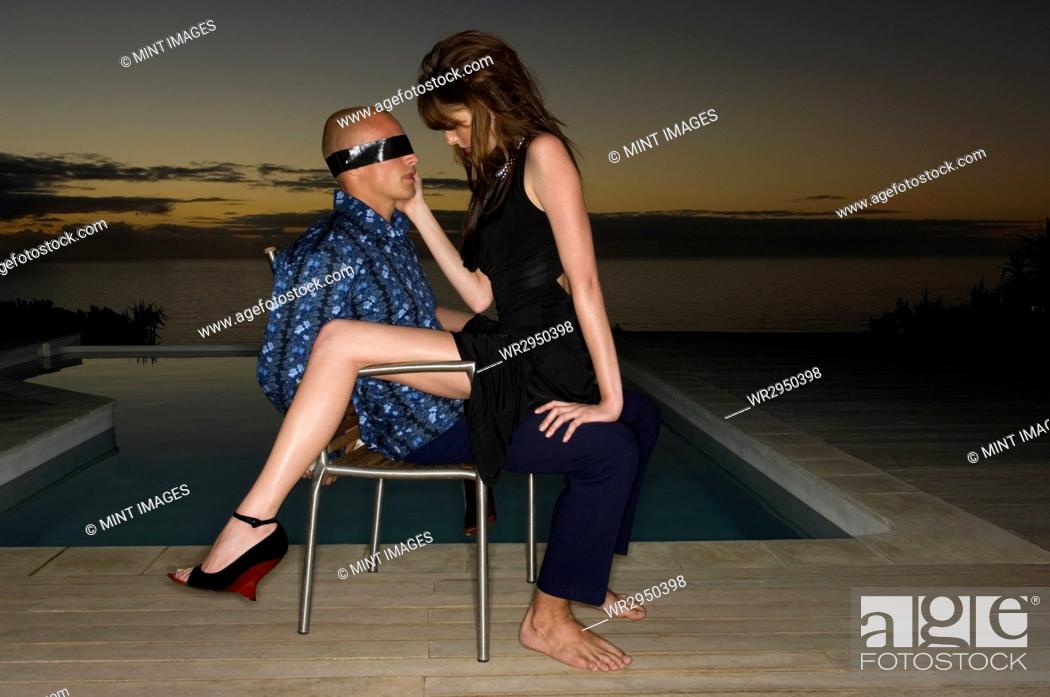 Stock Photo: Blindfolded man sitting on a chair beside a swimming pool, a woman sitting on his lap.