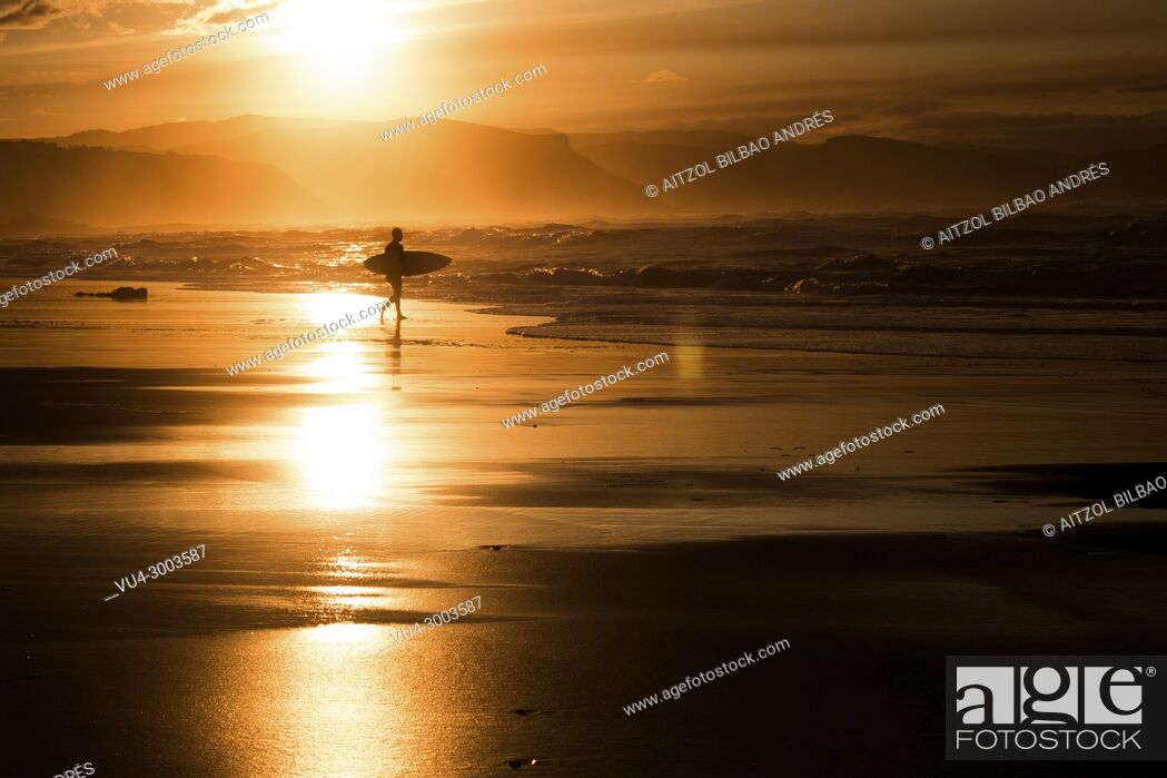 Stock Photo: Sunset surfer in Atxabiribil beach, Sopelana, Basque country. The Basque country is a perfect place for surfing with a lot of sand breaks.