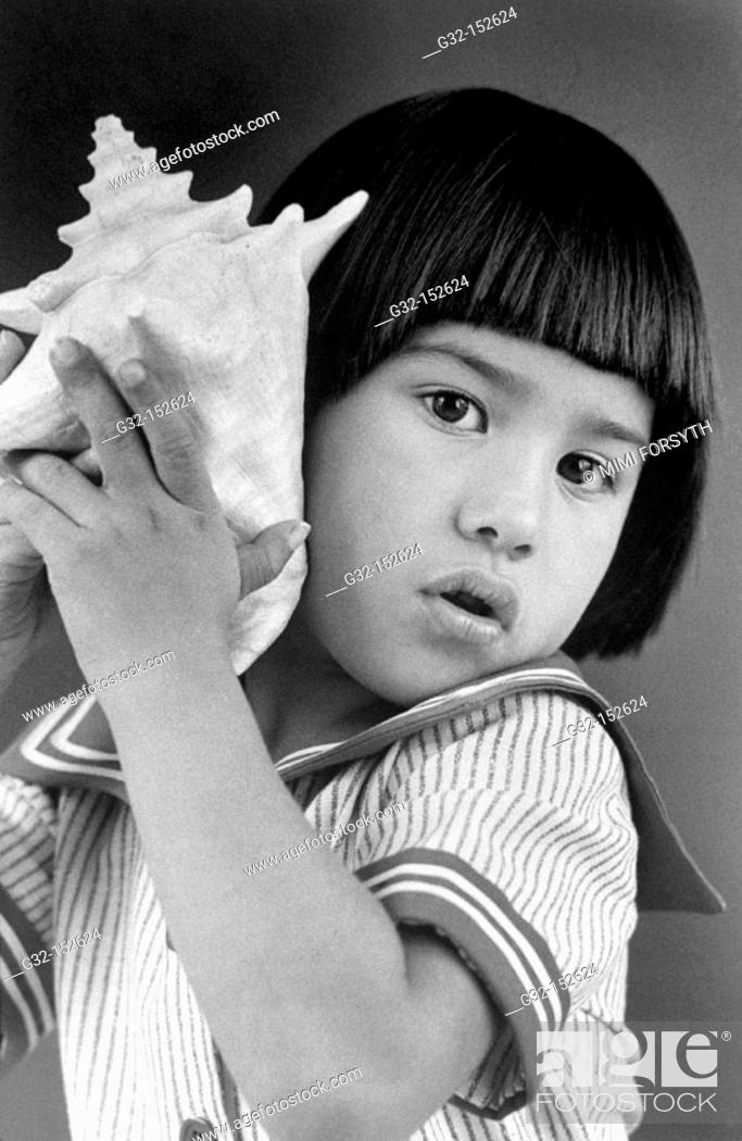 Stock Photo: Young girl listening to conch shell.
