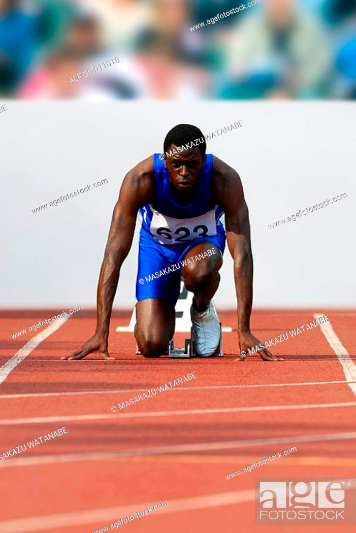 Stock Photo: Male Runner Crouched On Starting Blocks.