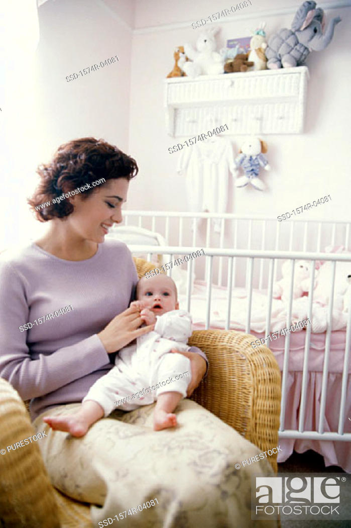 Stock Photo: Mother sitting with her baby boy in nursery.