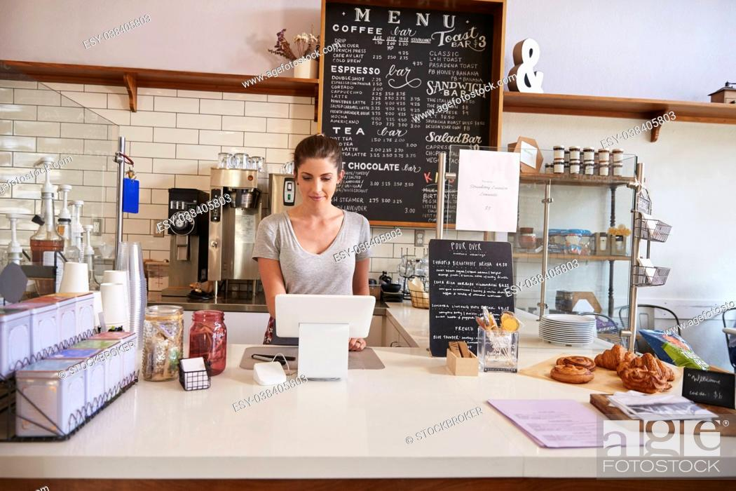 Stock Photo: Woman working on the till at the counter of a coffee shop.