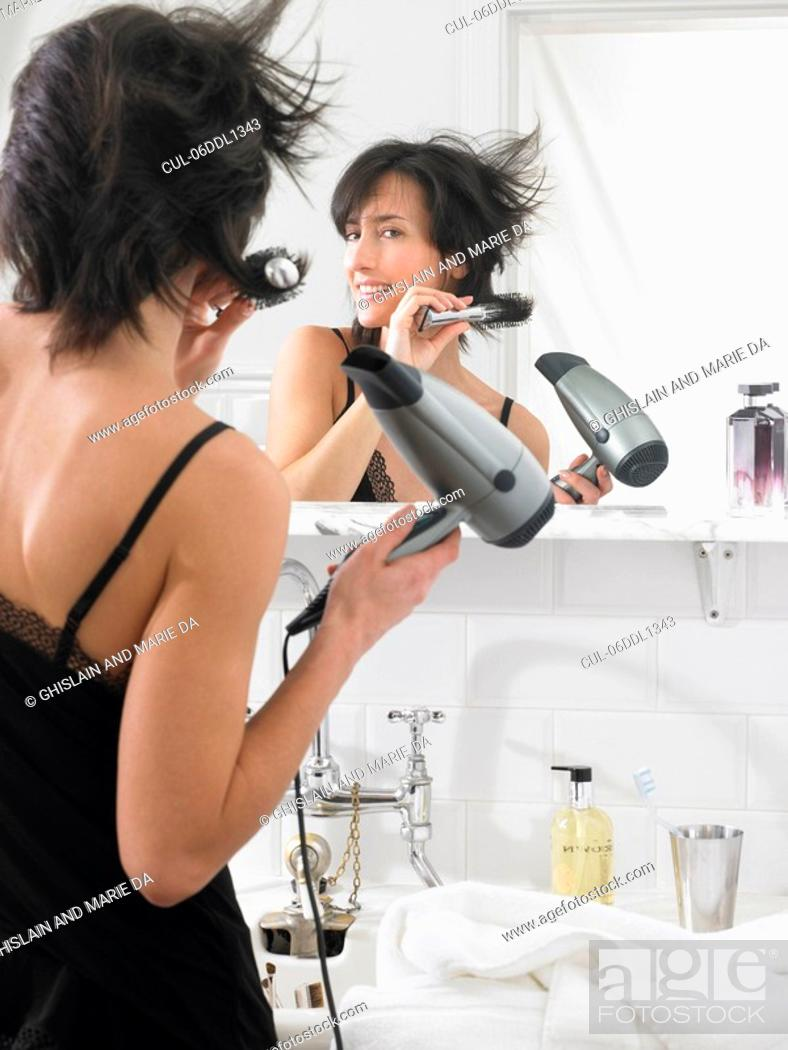Stock Photo: Woman drying her hair.