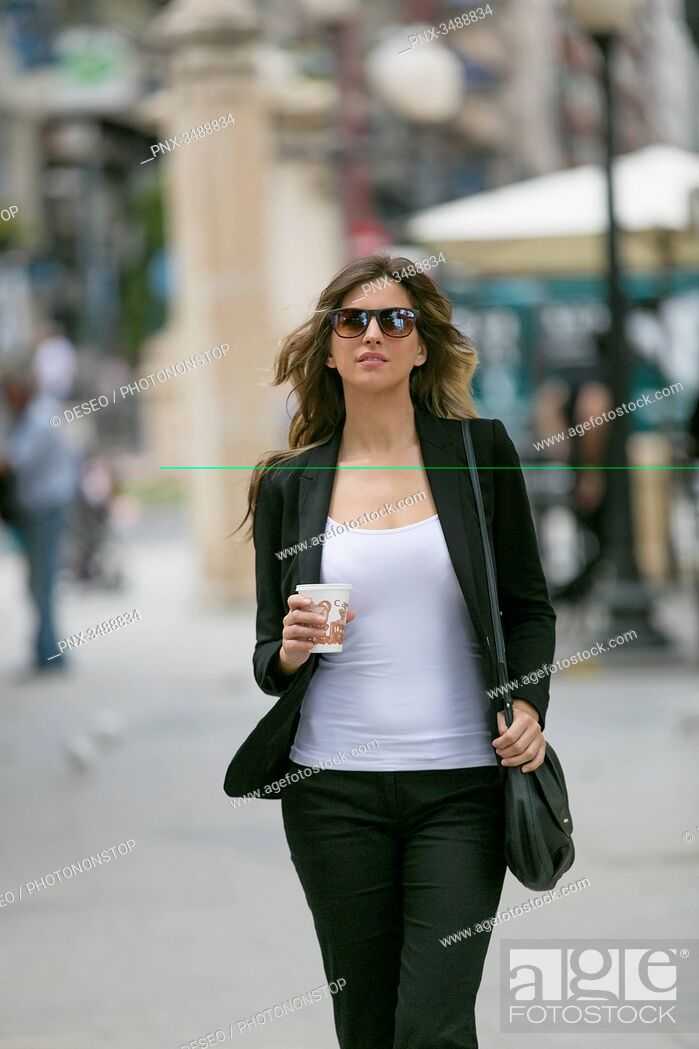 Imagen: Pretty young woman with sunglasses walking in downtown.