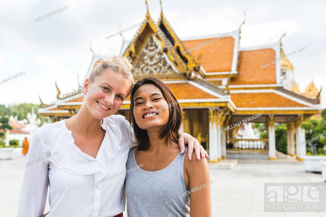 Stock Photo: Thailand, Bangkok, portrait of two smiling friends in front of temple.