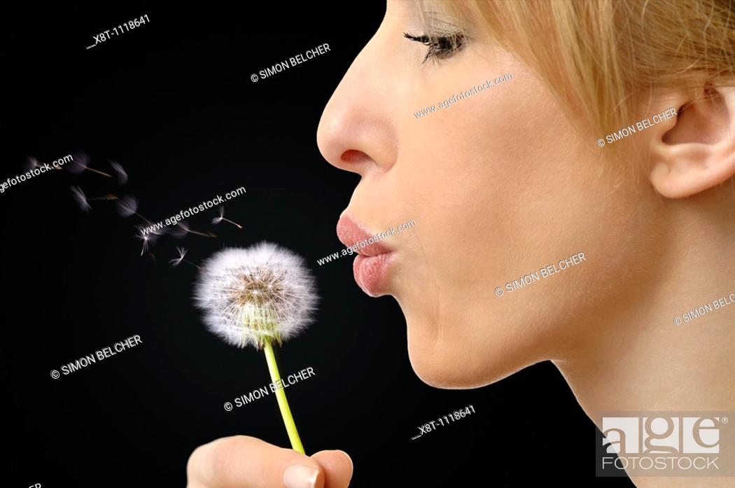 Stock Photo: Woman Blowing Dandelion Seeds.