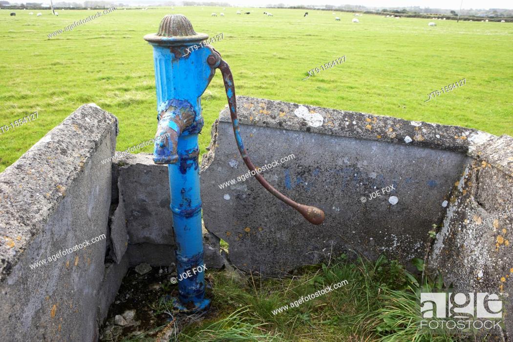 Stock Photo: old painted manual water pump field supply easkey county sligo republic of ireland.