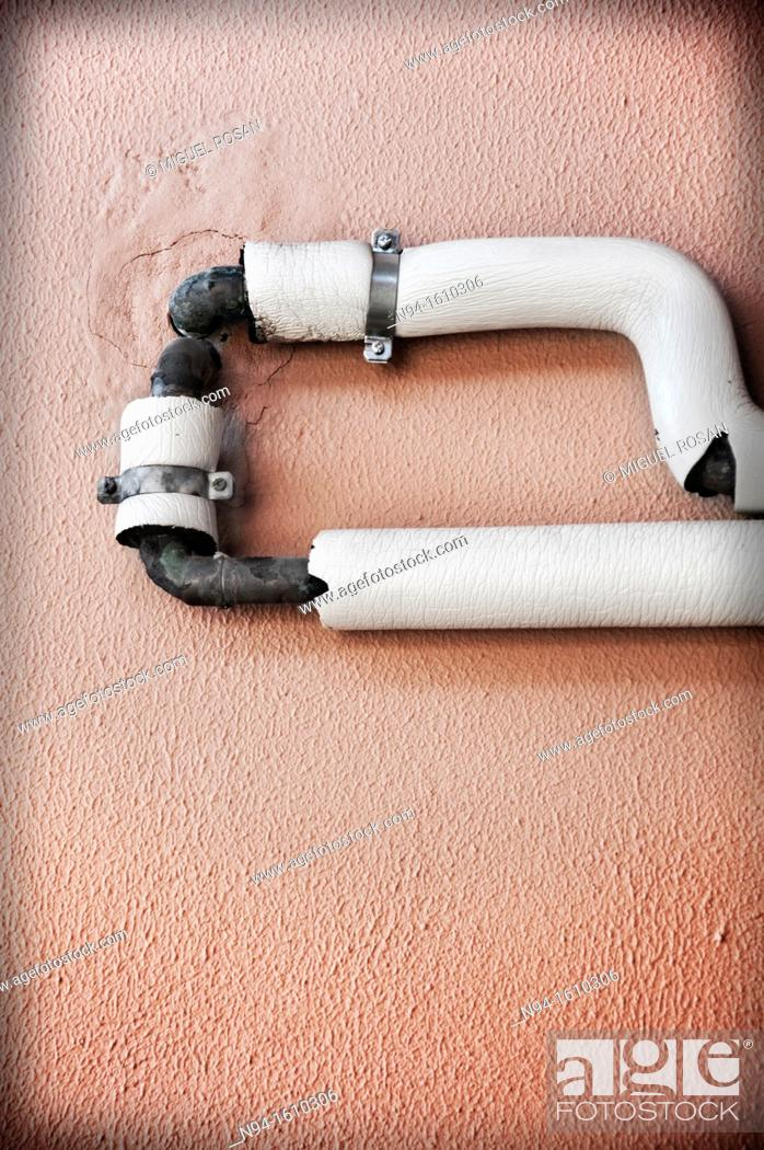 Stock Photo: Tubes attached to the wall for power.