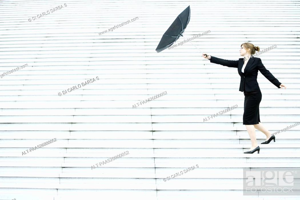 Stock Photo: Businesswoman struggling with umbrella in wind.