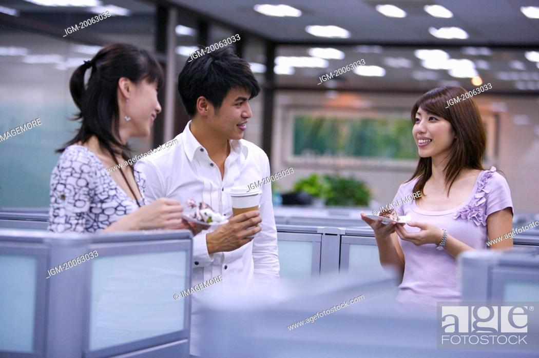 Stock Photo: Three colleagues eating or drinking at coffee break and talking with smile.