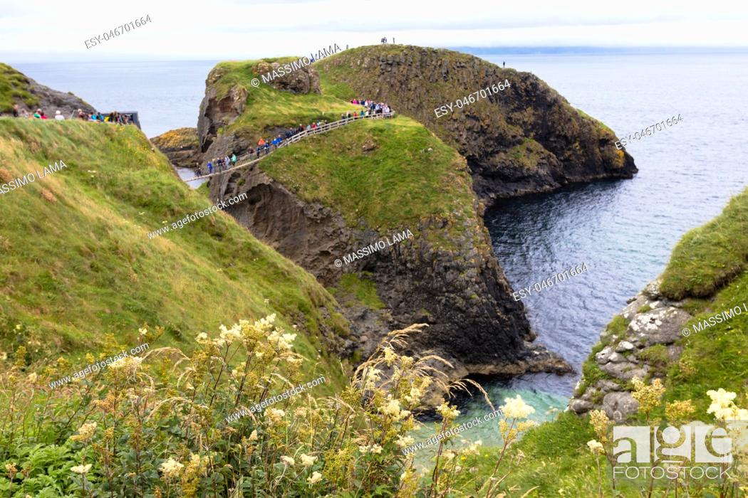 Stock Photo: Carrick-a-Rede Rope Bridge is a bridge near Ballintoy in County Antrim, Northern Ireland. The bridge links the mainland to the island of Carrickarede.