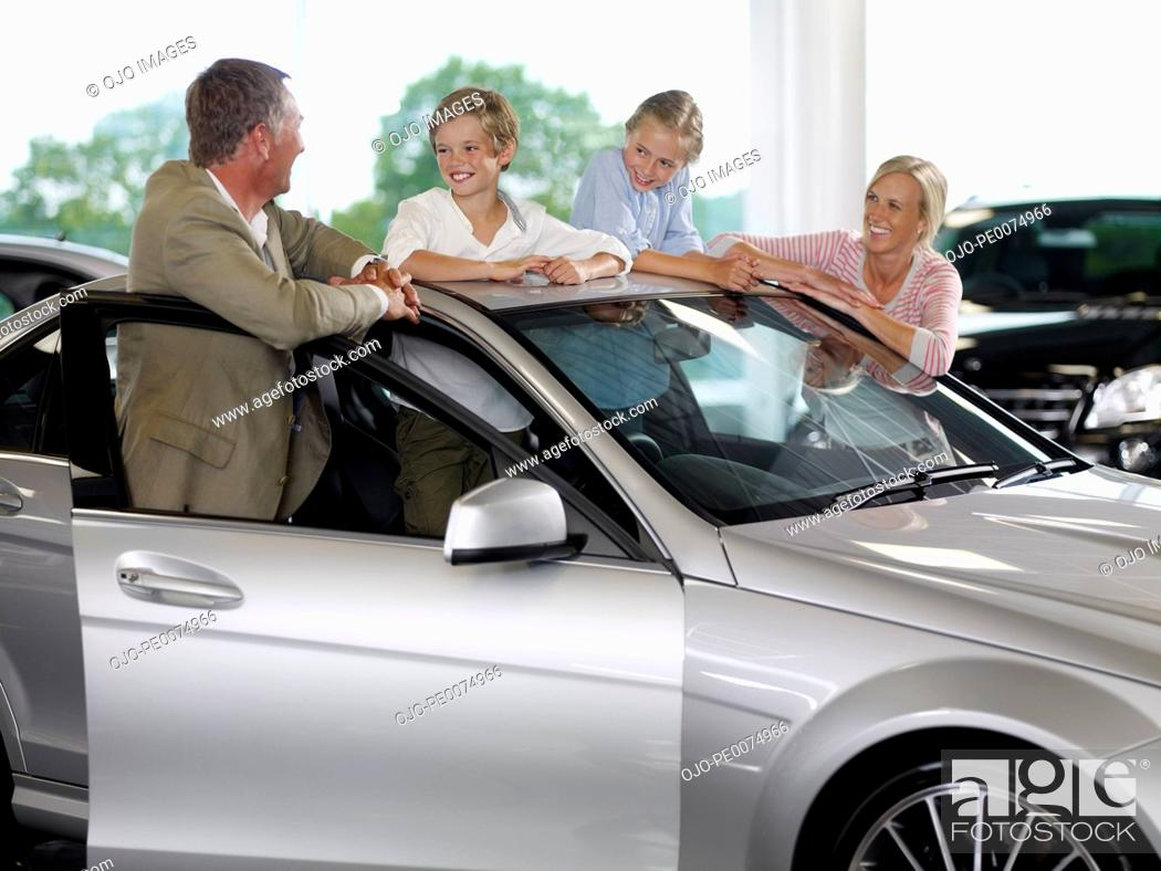 Stock Photo: Family looking at new car in showroom.