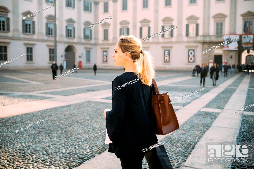 Stock Photo: Young female tourist with shopping bags in city square, Milan, Italy.