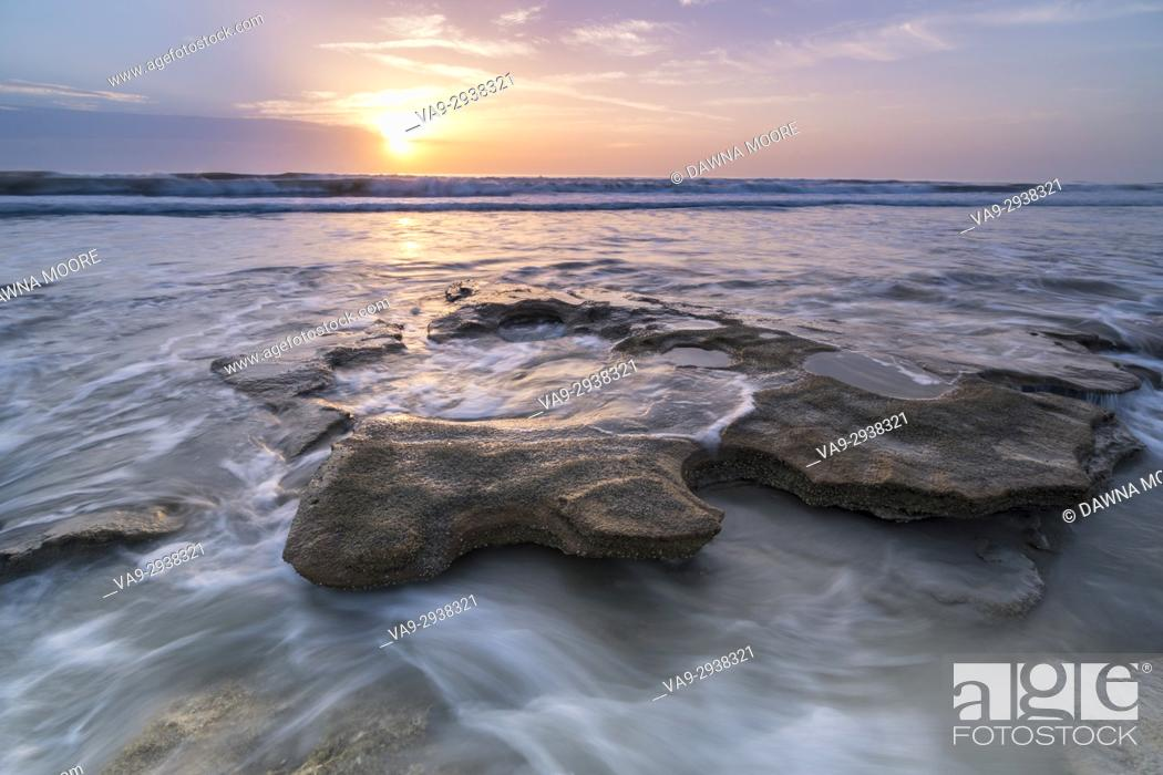 Stock Photo: Sunrise over the Incoming tide swirling around a coquina rock at Marineland Beach, Florida.
