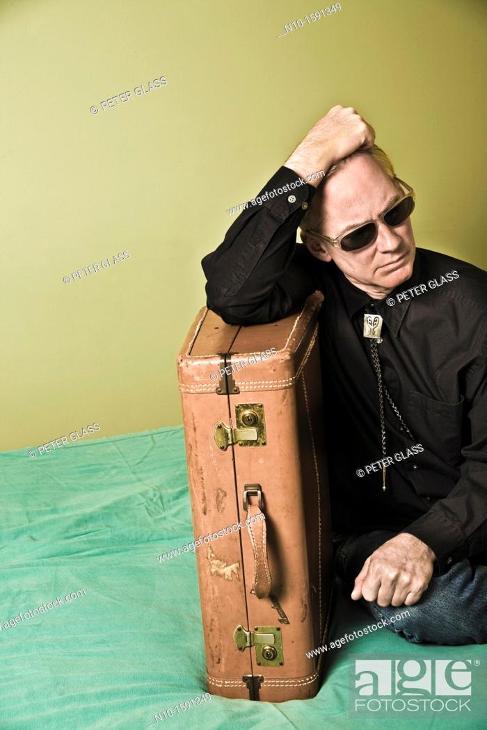 Stock Photo: Middle-age man sitting on a bed with a suitcase.