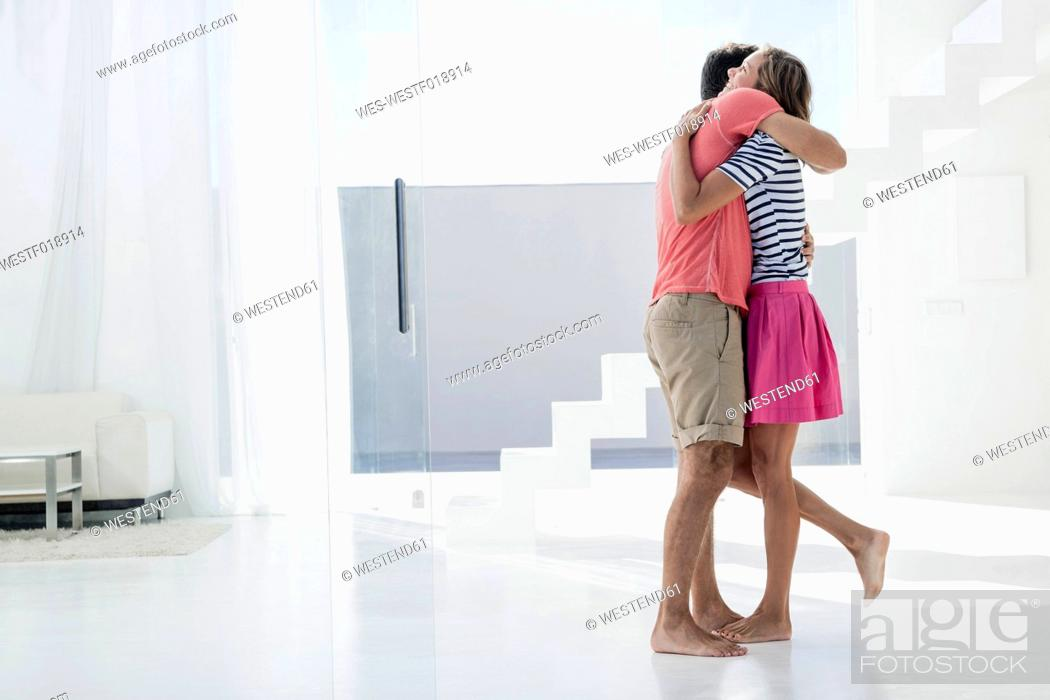 Stock Photo: Spain, Mid adult couple embracing in modern apartment.