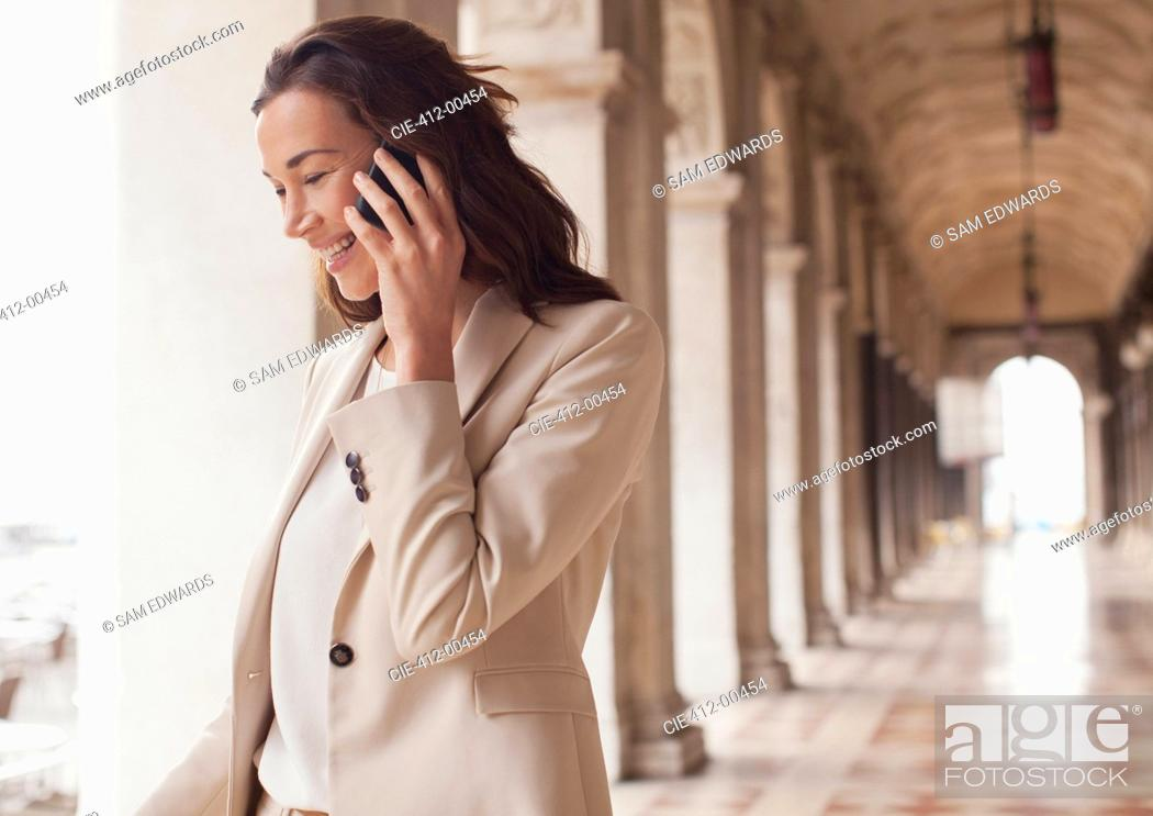 Stock Photo: Smiling businesswoman talking on cell phone in corridor.
