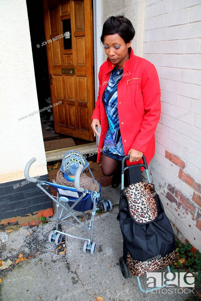 Imagen: Mother and toddler in buggy coming home from shopping.