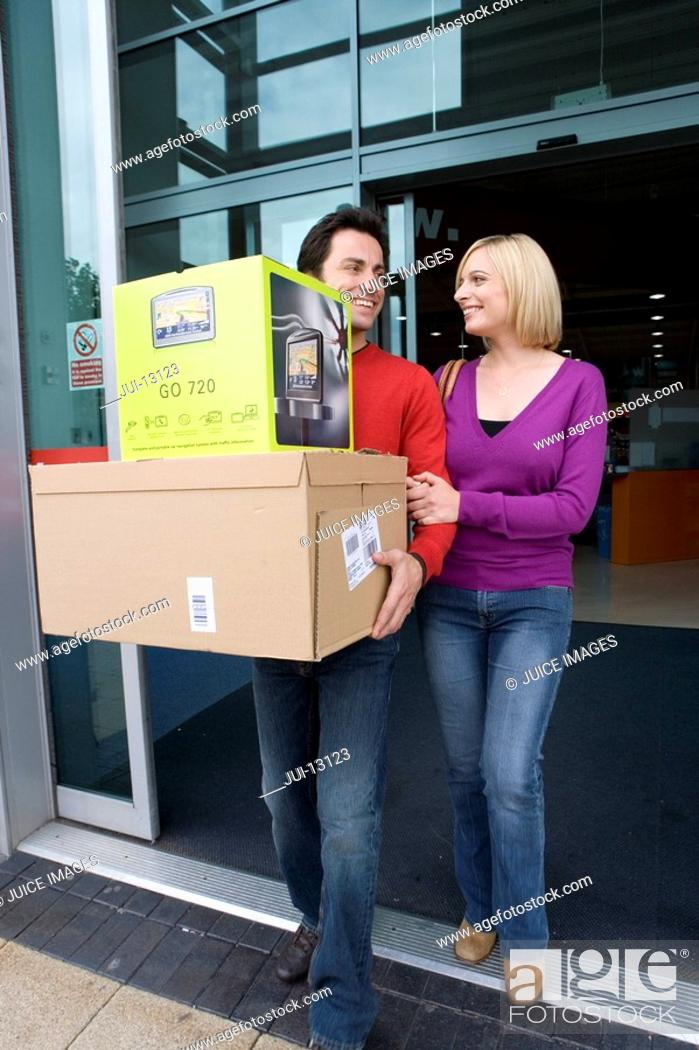 Stock Photo: Young couple leaving shop with boxes, smiling at each other, low angle view.