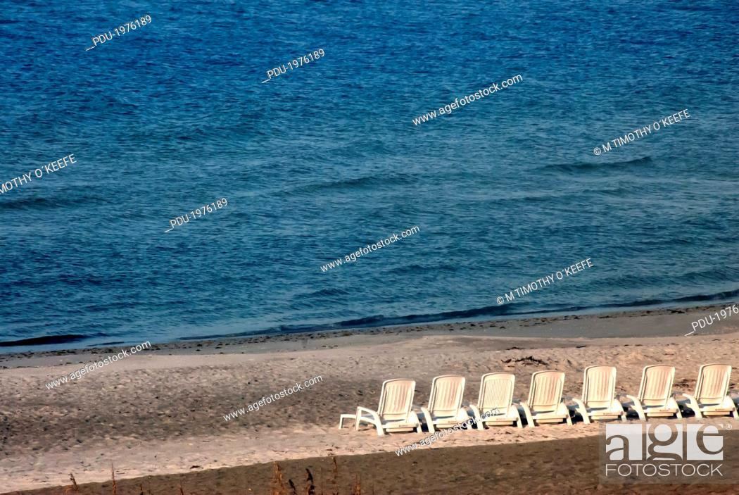 Stock Photo: A row of empty beach loungers on a beach.