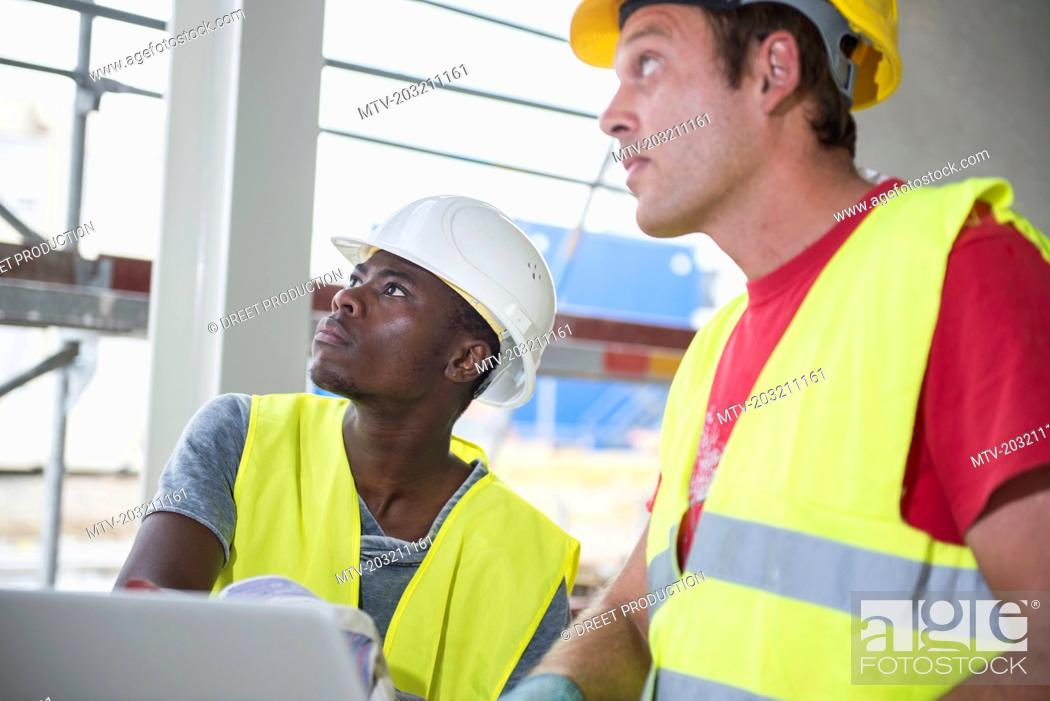 Stock Photo: Construction workers looking up at building site.