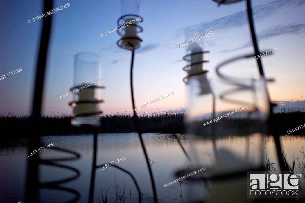 Stock Photo: Candles from a restaurant at dusk by the Albufera lake, near El Palmar, Albufera de Valencia Nature Reserve , Valencia, Spain.