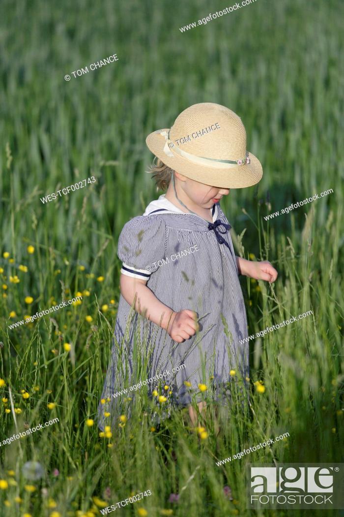 Stock Photo: Germany, Bavaria, Girl walking through spring meadow.