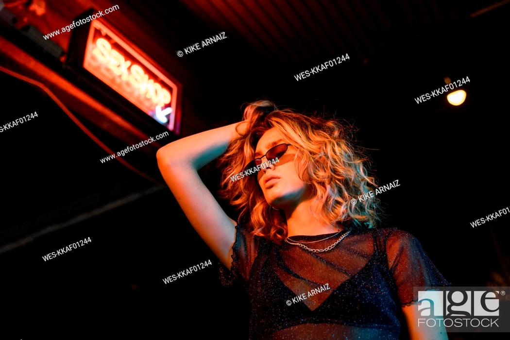 Stock Photo: Stylish young woman at night, standing in front of sex shop.