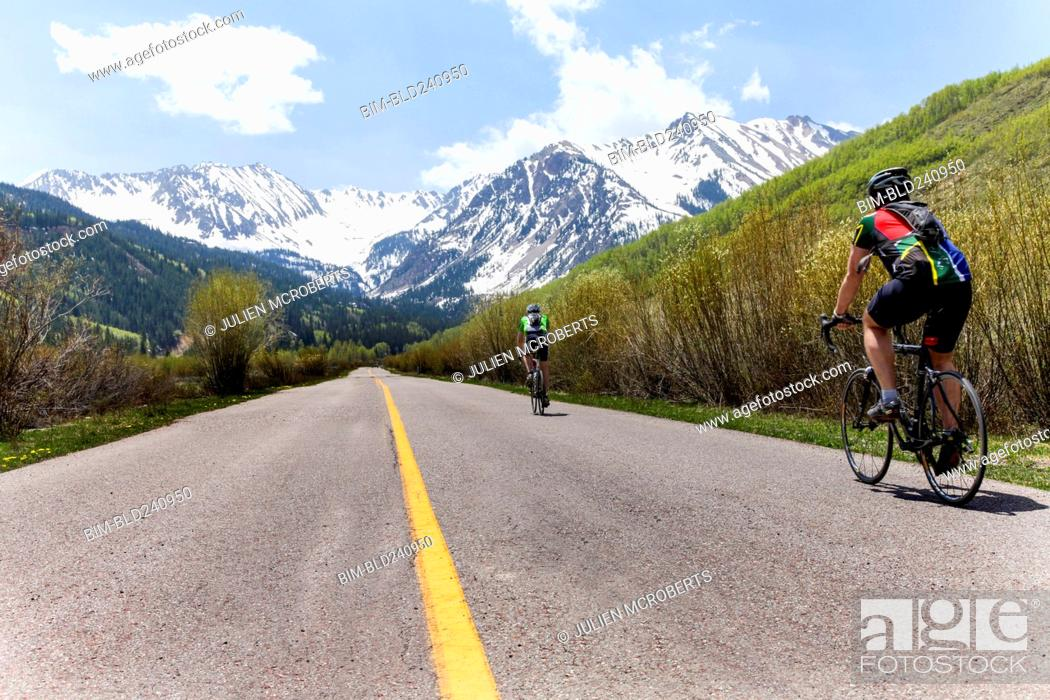 Stock Photo: People bicycling on road to mountain.