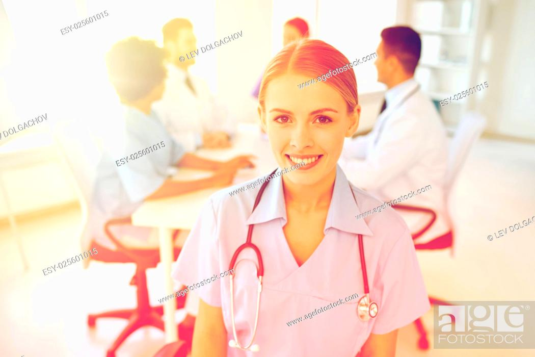 Stock Photo: health care, profession, people and medicine concept - happy female doctor or nurse over group of medics meeting at hospital.