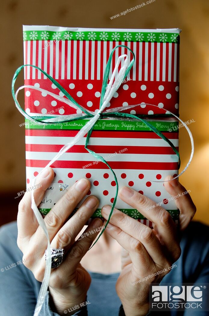 Stock Photo: Christmas Present in the hands covering the face.