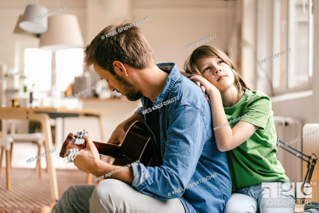 Imagen: Son leaning against father playing guitar at home.