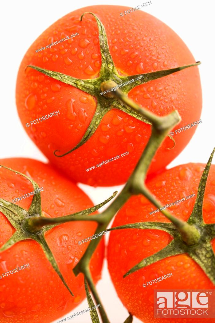 Stock Photo: Close up of wet red ripe tomatoes against white background.
