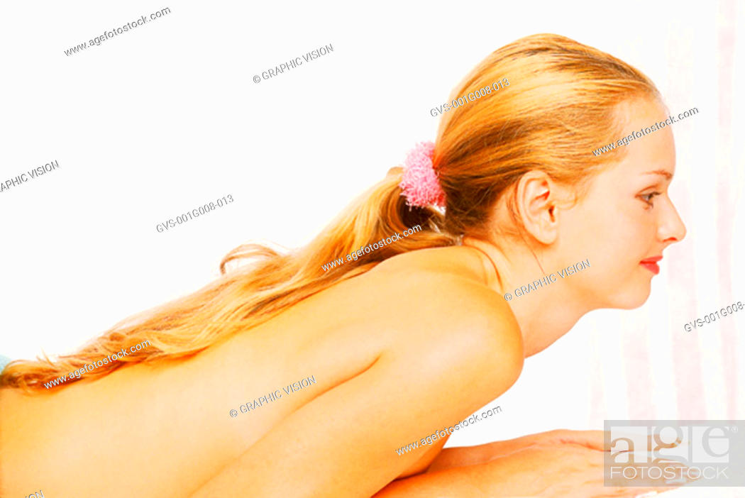 Stock Photo: Side view of a nude women lying on her stomach.