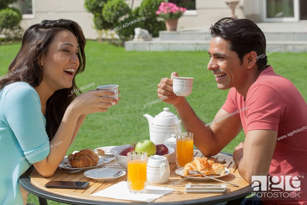 Stock Photo: India, Man and woman drinking coffee at breakfast table.