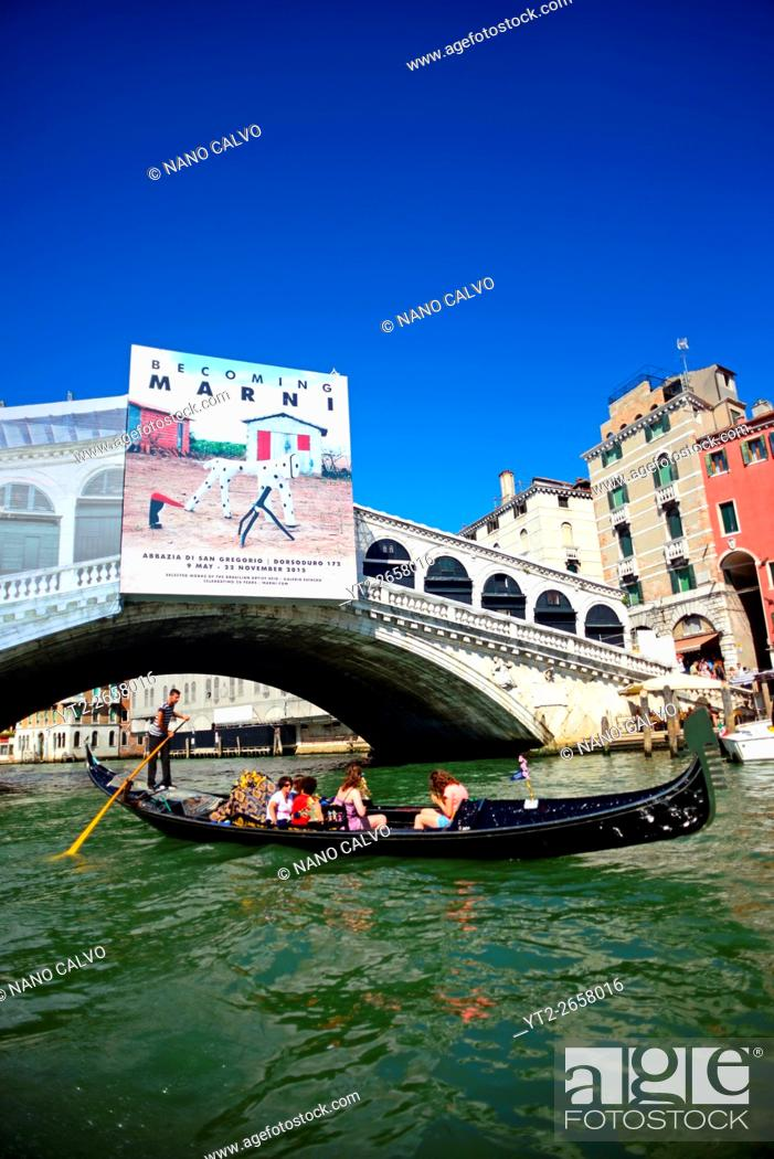 Stock Photo: Gondola ride in Grand Canal of Venice with La Biennale exhibition poster on bridge, Italy.