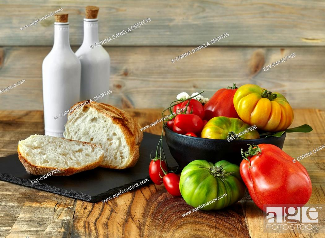 Stock Photo: Fresh yellow, red and green tomatoes inside black bowl with bread, oil and vinegar on slate and wood background.
