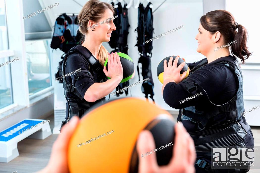 Stock Photo: Skinny and big woman having fun during ems training with medicine ball.