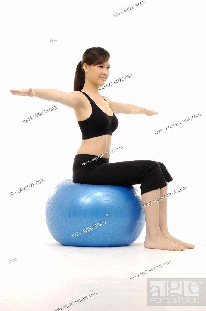 Stock Photo: young woman practicing yoga on exercise ball.