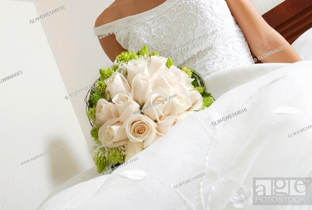 Stock Photo: Mid section view of a bride lying on the bed and holding a bouquet of flowers.