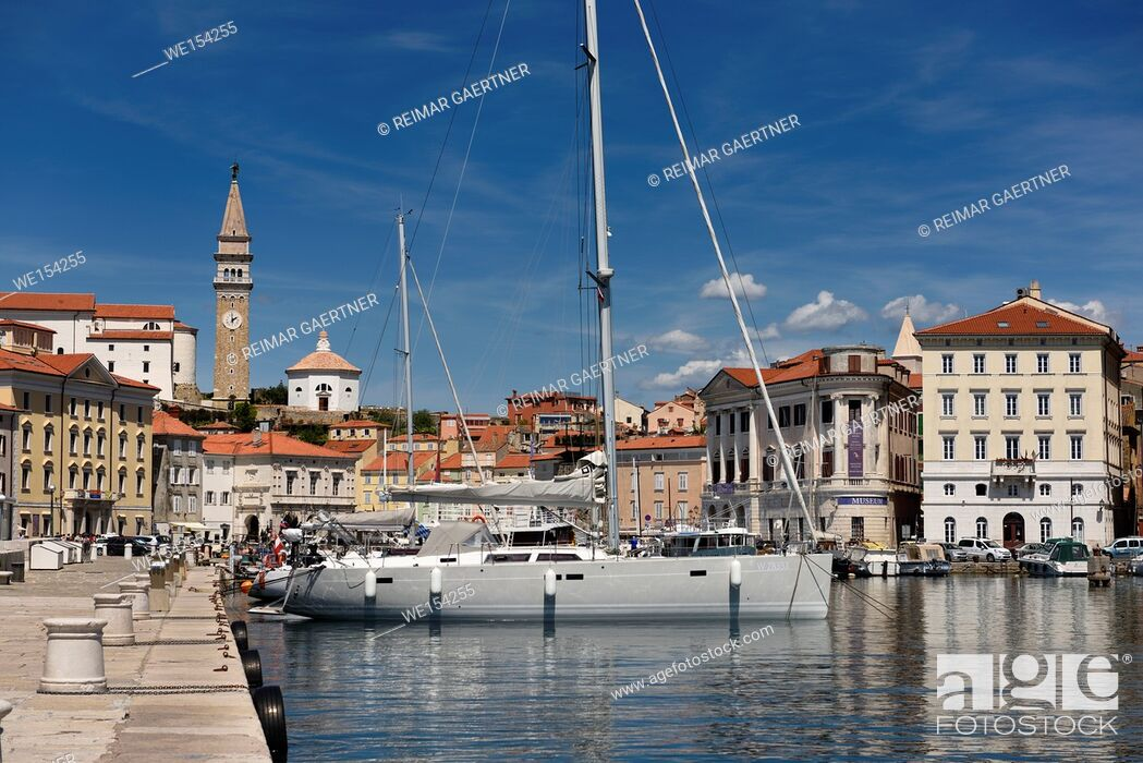 Stock Photo: Yachts and boats in the inner harbor of Piran Slovenia with Cathedral, belfry and baptistery of St George's church.