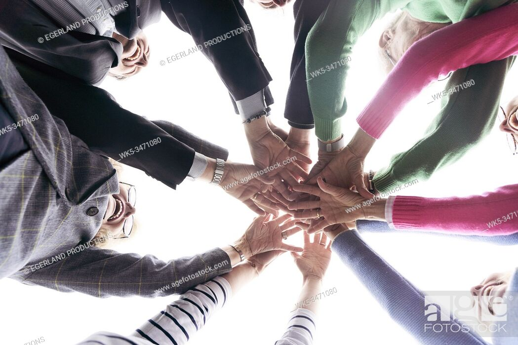 Stock Photo: Group of friends putting hands together, directly below image.