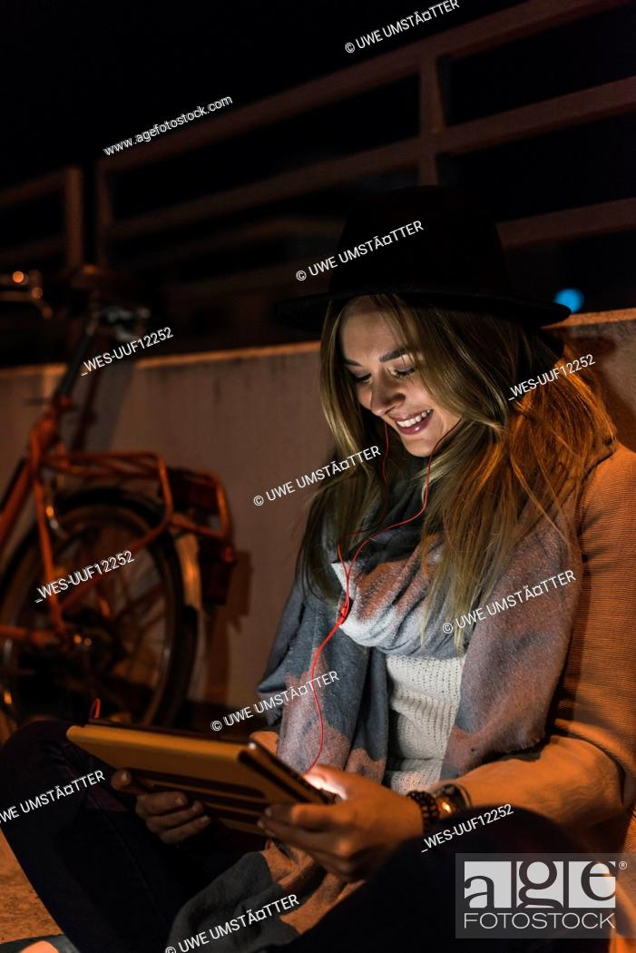 Stock Photo: Smiling young woman in the city using tablet at night.