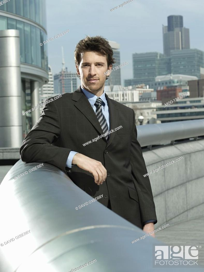 Stock Photo: Young businessman leaning on pipe outside building.
