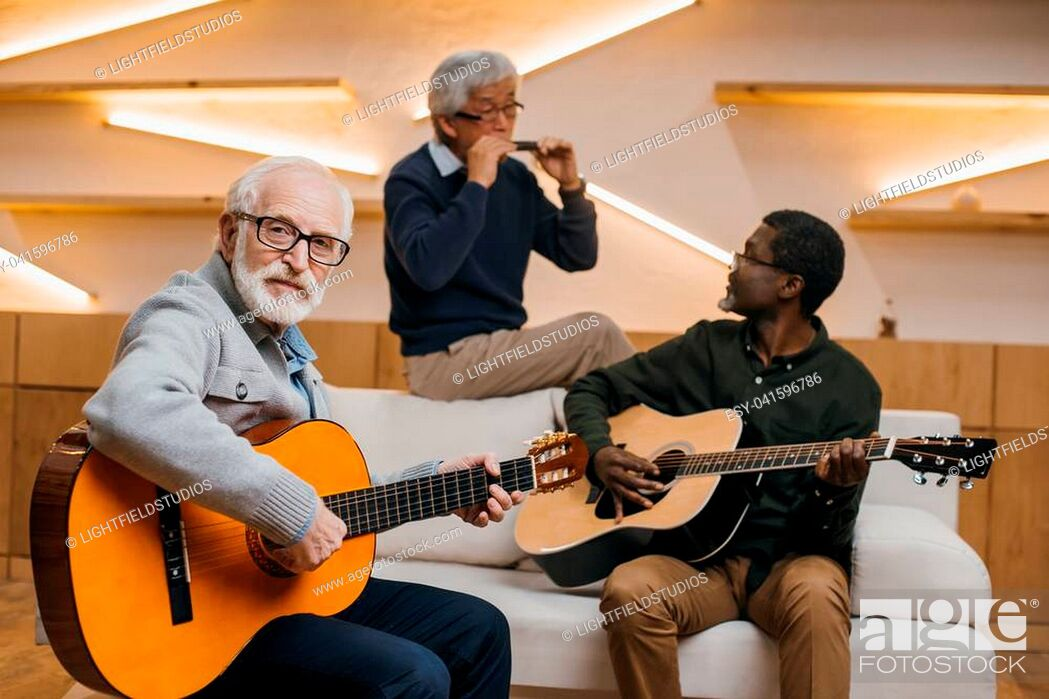 Stock Photo: group of handsome senior friends playing music with guitars and harmonica.